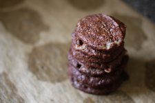 An image of a stack of chocolate cookies on a wooden table.
