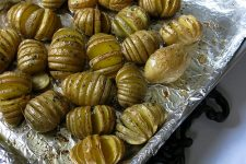 Cooked Saged Hasselback potatoes on a baking sheet | Foodal