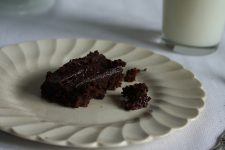 A close up view of a sliver of brownies in a white plate with a glass of milk beside it.