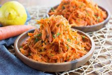 Horizontal image of two wooden bowls filled high with a carrot slaw on a roped placemat next to a lemon.