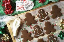 Horizontal image of decorated Christmas gingerbread cut-outs on a wooden board next to a piping bag and holiday decorations.