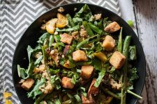Horizontal image of a plate of tofu and green bean salad on a patterned napkin.
