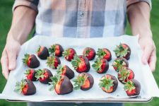 A man holds a tray of chocolate covered strawberries.