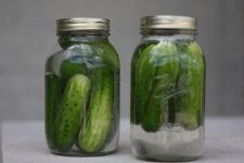 A close up image of two glass jars filled with delicious crunchy pickles.