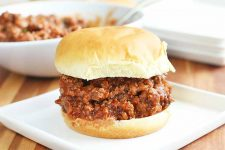 Sloppy joe ground beef sandwich with red sauce on a hamburger bun, on a white plate, with a bowl of more of the meat mixture and a stack of a few more plates in the background, on a brown wood surface.