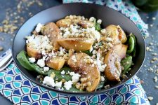 Horizontal image of a charcoal gray bowl containing a combination of baby spinach, honey-glazed peaches, crumbled goat cheese, and chopped walnuts, with more walnut bits scattered around the bowl on a gray surface, with a folded dark and light blue patterned cloth napkin, and a fork to the left of the frame.