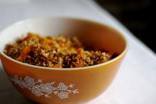 A close up view of an orange bowl filled with granola mixture.