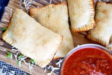Horizontal overhead image of four homemade pizza pockets with crimped edges, on a wooden cutting board with a small glass bowl of tomato sauce and scattered shredded mozzarella cheese and diced green bell pepper, on a dark blue and white cloth surface.