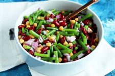 Horizontal image of a large white serving bowl with a bean salad.