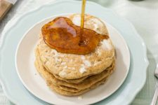 Horizontal image of vegan hotcakes with syrup poured on top of them.