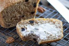 Horizontal image of a slice of pecan and blueberry bread spread with butter on a cooling rack.