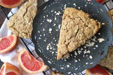 Horizontal image of a triangular slice of scone on a dark plate, with more scones and slices of fruit on the bottom.