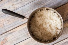 Top down view of a sauce pan full of fluffed, cooked rice on a weathered wooden surface.