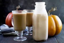 Horizontal image of a bottle of a light orange milky liquid next to pumpkins and glasses of coffee.