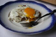 Eggs sunny side up on a toast on a ceramic plate.