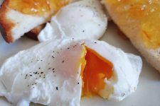 Closeup of a poached egg sprinkled with black pepper and broken open to show a vibrant orange soft-cooked center, on a white plate with another poached egg and white toast topped with orange marmalade.