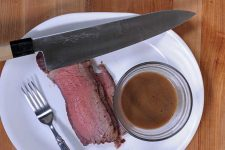 Top down view of a ceramic plate with a standing rib roast and a round glass serving dish full of au jus sauce | Foodal
