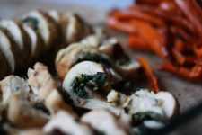 An image of delicious chicken roulade with thin strips of red bell pepper at the back.