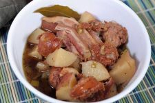 A close up view of an Irish Sausage, Bacon, Potato and Stout Stew in a white porcelain serving bowl.