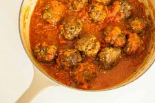 Top down view of a cooking pot full of Italian Meatballs with Red Sauce.