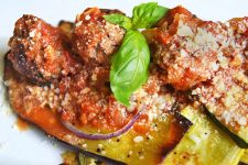 Closeup horizontal image of roasted zucchini, eggplant, and red onion with tomato sauce, meatballs, and grated cheese, garnished with a sprig of basil, on a white ceramic plate.