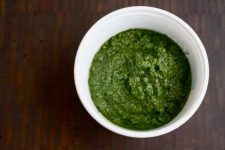 A white ceramic bowl of Kale Almond Pesto. sitting on dark wooden table.