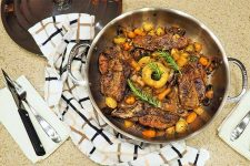 Top view of a large stainless steel pan filled with cooked meat and vegetables, surrounded by a white, black, and beige kitchen towel on a beige countertop, with steak knives and forks on white napkins to the left and right of the pan.