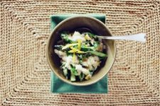 A top view image of a bowl of lemon asparagus risotto on top of a weaved table mat.