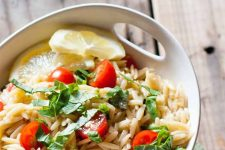 Closely cropped image of orzo pasta salad with halved cherry tomatoes, chopped basil, and slices of lemon, on a brown wood surface.