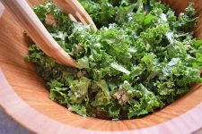 Horizontal closely cropped image of kale salad with Pecorino cheese in a large wooden salad bowl, with wooden salad tongs.