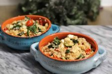 Two terra cotta handled bowls with a light blue and darker blue glaze, filled with a mixture of quinoa, vegetables, and feta, on a marble surface with a bunch of kale in soft focus in the background.