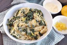 A white bowl of noodles and greens on a blue and white cloth, with a fork, two small white bowls of citrus zest and grated Parmesan cheese, and a whole lemon, on a dark brown wood surface.
