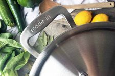 Horizontal close up image of a pot handle surrounded by vegetables and fruits