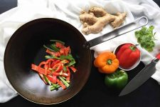 Horizontal image of a pan with assorted peppers next to more peppers, ginger, and a knife on a white towel.