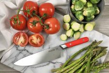 Horizontal image of a marble cutting board with sliced tomatoes, Brussels sprouts, and asparagus with a knife with a red handle.