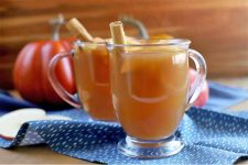Two glass mugs of mulled apple cider punch, with cinnamon sticks for garnish, on a gathered blue table runner with a pattern of white spots, on a wood table and against a brown wood backdrop, with sliced and whole apples and plastic pumpkin decorations in the background.
