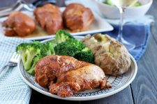A white plate with a black decorative pattern is topped with barbecue chicken breast, a baked potato, and steamed broccoli, with a folded blue and white cloth napkin and silverware to the left, and a serving platter of chicken beside a bowl of vegetables with a glass of white wine in soft focus in the background, on a blue cloth on top of a dark brown wood table.