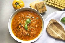 Horizontal overhead image of a white ceramic bowl of yellow tomato sauce with a sprig of fresh basil for garnish, on an off-white surface with a white cloth, a wooden spoon, a stack of uncooked pasta, a few hunks of Parmesan cheese with yellowish rinds, and a yellow tomato with a green top.