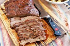 Sliced beef brisket arranged at an angle on a wooden cutting board with a carving knife, on a striped multicolored cloth with a white bowl of roasted potatoes visible just at the edge of the frame.