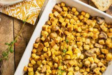 Horizontal image of a rectangle casserole dish filled with bread cubes and vegetables with fresh thyme.