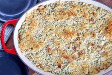 A red and white ceramic casserole dish is filled with a just-baked vegetable side topped with toasted breadcrumbs, with two dark blue plates in the background.