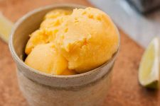 A close up view of a mango lime and cream cheese sherbet in a small stoneware bowl.