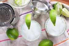 Overhead horizontal shot of two margaritas with lime wedge garnishes, with more of the citrus fruit and a stainless steel cocktail shaker and strainer on a white cloth with purple, pink, and orange stripes, on top of a brown wood surface.