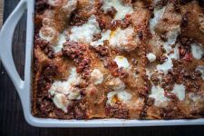 Close up of a white ceramic baking dish full of a meaty lasagna.