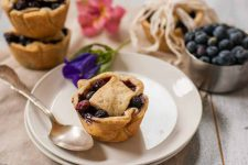 Oblique view of single mini blueberry pie on a white ceramic plate with additional mini pies in the background.