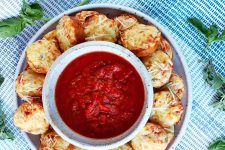 Overhead closely cropped horizontal shot of a gray plate of homemade mini pizza bites arranged in a circle around a white bowl of red tomato sauce, on a blue and white checkered cloth with scattered sprigs of fresh basil.