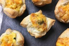 Horizontal image of mini quiches on a slate.