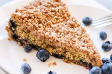 Closeup of a single slice of 100% whole wheat vegan cinnamon blueberry coffeecake on a white ceramic saucer with a few fresh berries sprinkled randomly.