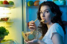 An attractive lady is caught late at night with the refrigerator door open and eating food with a guilty look on her face. | Foodal.com