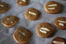 A close up image of round spiced cookies with slivers of almonds on top.